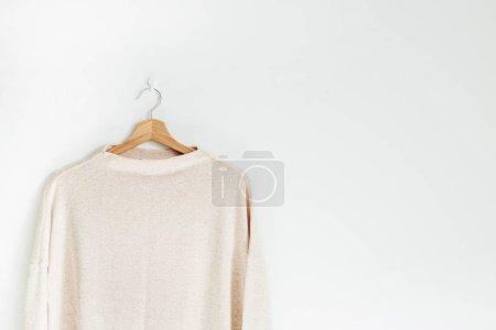 Photo pour Pull femme pastel sur cintre au mur blanc. Femme mode vêtements concept . - image libre de droit