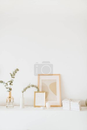Photo pour Composition design d'intérieur stylisé. Cadre photo, branche d'eucalyptus, vase sur table blanche. Salon scandinave branché . - image libre de droit
