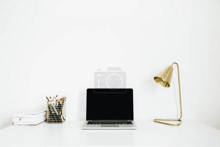Photo pour Siège social bureau espace de travail portable, lampe d'or, articles de papeterie sur fond blanc. Concept de design minimaliste d'intérieur moderne. Bureau mock up. - image libre de droit