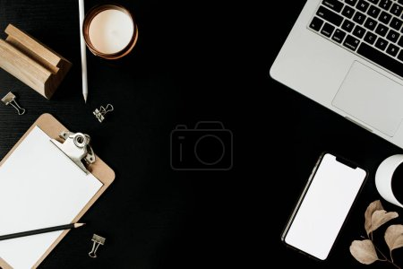 Photo for Frame of laptop, clipboard, cell phone with copy space screen and decoration on black background. Flat lay, top view home office workspace. Blog / website hero header mockup. - Royalty Free Image