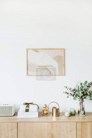 Photo pour Concept de design intérieur moderne. Salon de style scandinave Nordic minimal avec cadre photo sur le mur blanc, table en bois avec boîte-cadeau, un bouquet floral avec eucalyptus, bougies, radio. Pastel appartement à louer. - image libre de droit