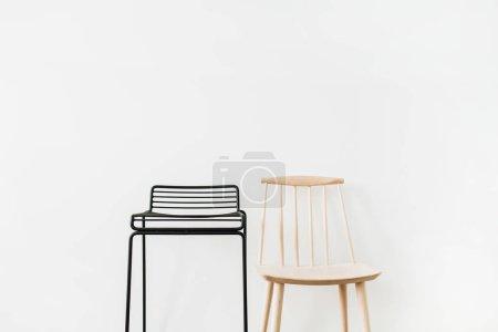 Foto de Taburete de metal negro, silla de madera en pared blanca. Concepto de diseño moderno muebles escandinavos mínimo. - Imagen libre de derechos