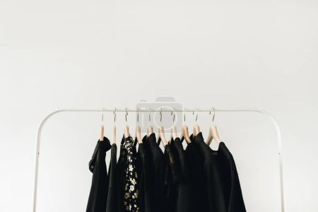 Photo for Minimal fashion clothes concept. Black female blouses and t-shirts on hanger on white background. - Royalty Free Image