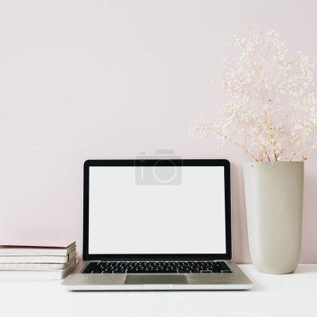 Photo pour Ordinateur portable et bouquet de fleurs sur fond rose. Vue frontale minimaliste espace de travail moderne bureau à domicile. Écran vide maquette tête de héros. Blog, médias sociaux, modèle de site Web. Fille patron concept . - image libre de droit