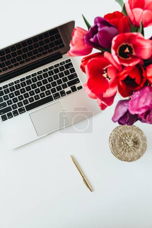 Photo for Home office workspace background with laptop, tulip flowers bouquet. Flat lay, top view lady boss minimal work concept. - Royalty Free Image
