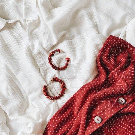 Photo pour Mode concept féminin français. Chemise blanche de belle femme, jupe rouge foncé et magnifiques boucles d'oreilles rouges faites de coraux couchés sur le lit avec draps blancs . - image libre de droit