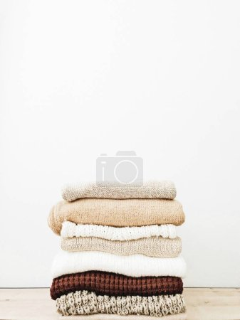 Photo for A minimal stack of warm beautiful feminine sweaters or pullovers lying on wooden table agains white wall. Autumn, fall, winter, fashion concept. Empty space, mock up. - Royalty Free Image