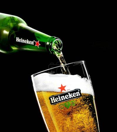 POLTAVA, UKRAINE - MARCH 22, 2018: A Glass of beer Heineken Lager on a black background.Heineken Lager Beer is a pale lager beer produced by the Dutch brewing company Heineken International