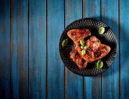 Barbecue on the grill chicken wings on a plate on a wooden background