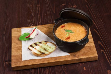 Photo for Soup in pant served on wooden board with bread - Royalty Free Image