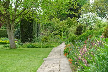 Scenic View of Stone Paved Path trough Grass Lawn and Flower Bed in Garden