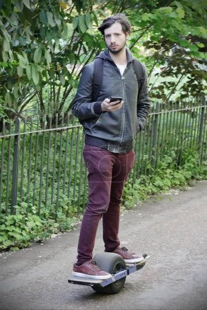 Photo for Young handsome man in casual clothes with hoverboard and phone - Royalty Free Image