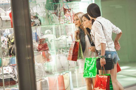 Young cheerful women near the showcase. Smiling girlfriends doing shopping together