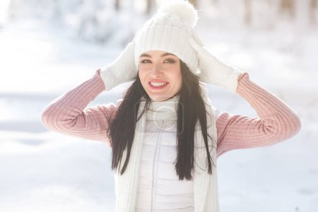 Close up portrait of young beautiful woman in the winter wood. Attractive lady smiling at camera
