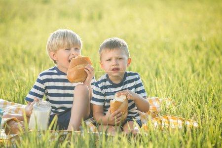 Photo pour Enfants mignons boire du lait et manger du pain - image libre de droit