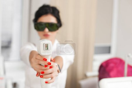 Photo pour Cosmetologue avec épilateur laser. Thérapie par épilation laser. Salon de dermatologie. Procédure d'épilation . - image libre de droit