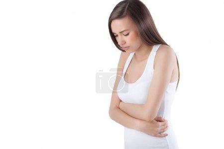 Photo pour Femme sur fond blanc isolé ayant mal à la tête ou à l'estomac. Femme gros plan se sentant malade. Dame ressent la douleur . - image libre de droit