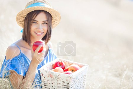 Photo for Cute young woman with apples outdoors. Summer background. - Royalty Free Image