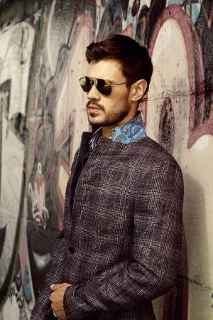 Photo for Stylish man in sunglasses and trendy jacket posing on graffiti wall - Royalty Free Image