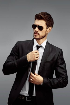 Photo for Stylish man in sunglasses and black suit on grey background - Royalty Free Image