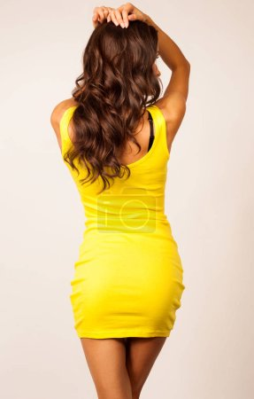 Photo for Rear view of woman posing in yellow dress - Royalty Free Image