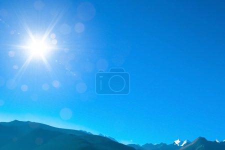 Blue sky with sunny sun and mountain.
