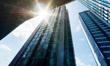 Low angle view of common modern business skyscrapers with sun flare .