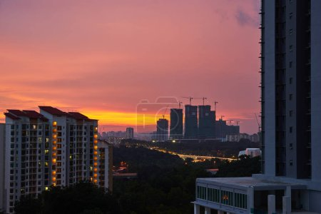 High buildings under construction with cranes at evening with modern apartment living block of flats buildings .