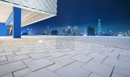 Photo for Perspective view of empty floor with modern building exterior and cityscape skyline. Night scene - Royalty Free Image