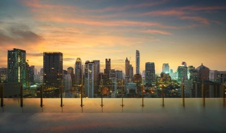 Photo for Cityscape sunset view of Bangkok modern office business buildings and high skyscrapers in business district. view from  swimming pool at Bangkok,Thailand. - Royalty Free Image
