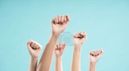 Photo for Multiethnic male and female hands raised against a blue background - Royalty Free Image