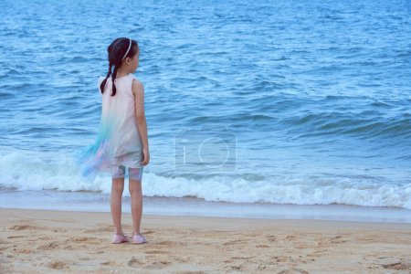 Photo for Lovely asian little girl in a pink shirt on tropical beach, travel vacation concept. - Royalty Free Image
