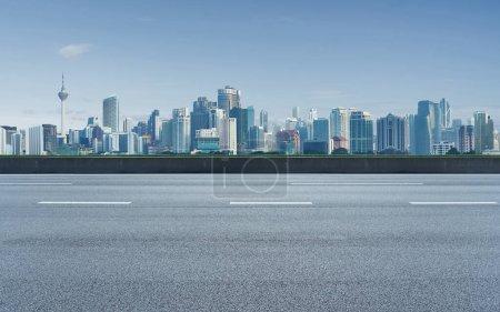 Photo pour Route asphaltée vide avec arrière-plan de la ville, scène de jour. - image libre de droit