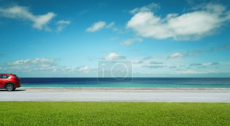 Photo for Electric SUV red car parked on road side with beautiful seacoast. - Royalty Free Image