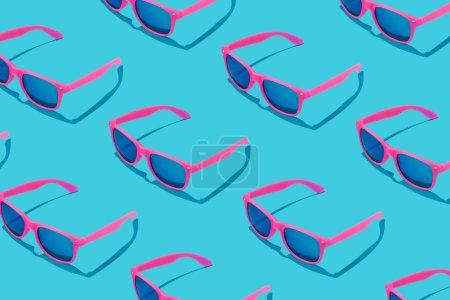 Foto de Patrón de gafas de sol color rosa sobre fondo azul pastel, concepto de verano mínimo - Imagen libre de derechos
