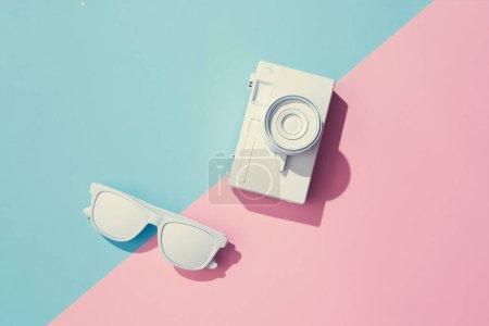 Photo pour Mise en page créative faite de caméra peinte et de lunettes de soleil sur fond rose pastel et bleu, concept exotique d'été minimal - image libre de droit