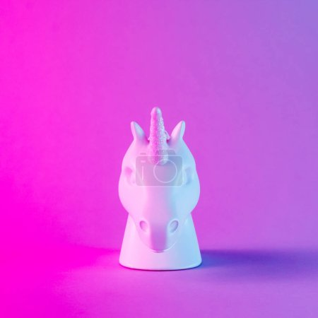 White painted unicorn head in bold pink and blue neon colors on gradient background. Minimal art fantasy concept.