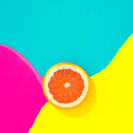 Creative tropical layout with grapefruit and colorful vivid papers. Abstract colors art background. Minimal summer concept. Flat lay.