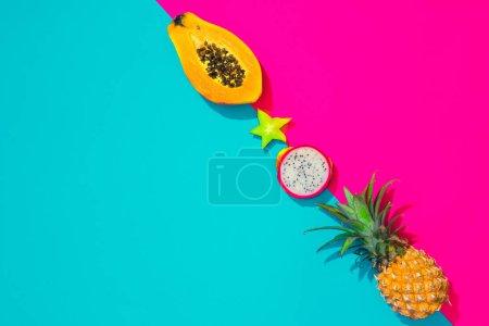 Foto de Creativo diseño tropical con frutas tropicales y papeles vivos colores. Fondo de arte abstracto de colores. Concepto de verano mínimo. Endecha plana. - Imagen libre de derechos
