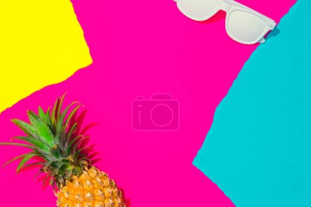 Creative tropical layout with pineapple, sunglasses and colorful vivid papers. Abstract colors art background. Minimal summer concept. Flat lay.