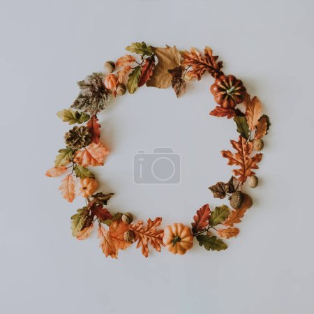 Creative autumn wreath made of yellow fallen leaves and nuts. Minimal flat lay. Nature concept.