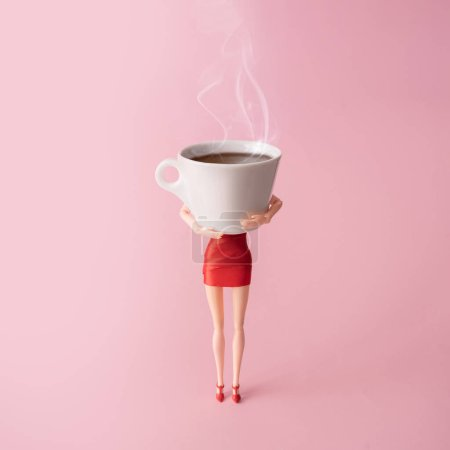 Girl doll in red dress holding big steaming cup of coffee against pastel pink background. Minimal coffee addiction concept