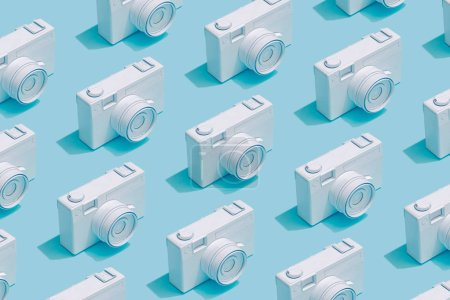 Pattern composition of vintage cameras on pastel blue background. Minimalist isometric concept.
