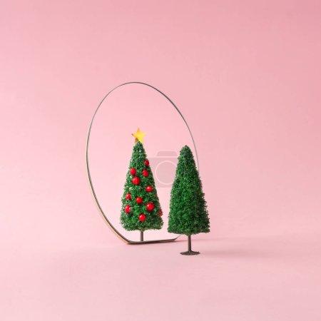 Photo pour Arbre de Noël réfléchissant sur miroir sur fond rose pastel. Minimal concept de décoration Nouvel An . - image libre de droit
