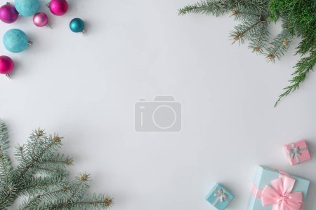 Photo for Creative layout made of colorful Christmas decorative balls and gifts with green fir branches on white background. Minimal winter holidays concept - Royalty Free Image
