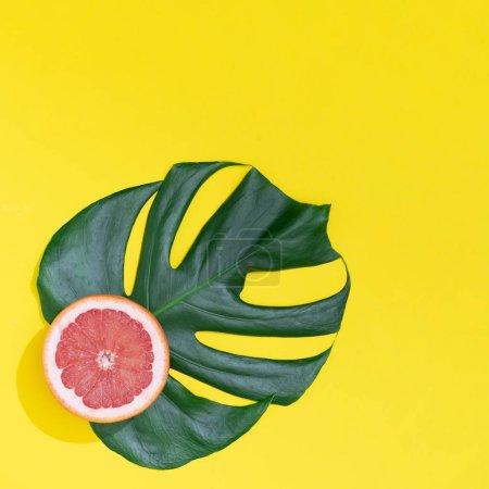 Photo pour Feuille de monstère avec pamplemousse rouge sur fond jaune vif. Concept d'été minimal - image libre de droit