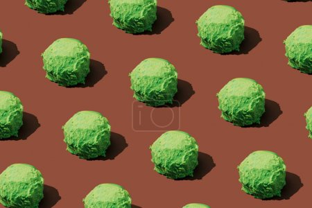 Photo for Green ice cream scoops pattern on brown background. Minimal summer food concept. - Royalty Free Image