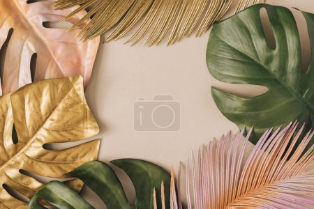 Photo for Creative layout made of golden and green tropical palm leaves on pastel beige background. Minimal summer exotic concept - Royalty Free Image