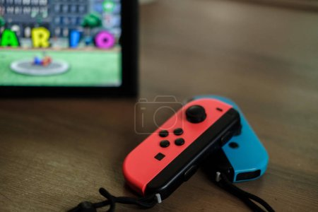 Anapa, Russian Federation - 17 July 2018: Joy-con controllers and console Nintendo Switch on table indoor, gamepad and video game console for home or portable gaming. Screen showing game Mario Odyssey