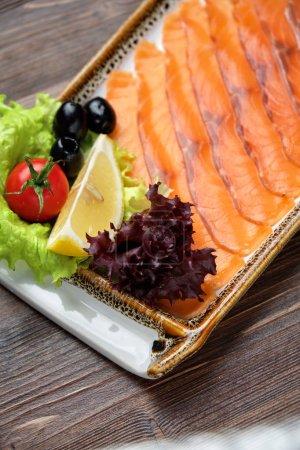 Photo pour Poisson de truite rouge tranché décoré avec des légumes dans une belle portion sur une plaque rectangulaire blanche. menu du restaurant - image libre de droit